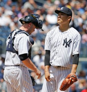 New York Yankees catcher Brian McCann, left, joints starting pitcher Masahiro Tanaka on the mound as Tanaka reacts after allowing a second-inning, two-run, single to Detroit Tigers designated hitter Victor Martinez in a baseball game at Yankee Stadium in New York, Sunday, June 21, 2015. (AP Photo/Kathy Willens)